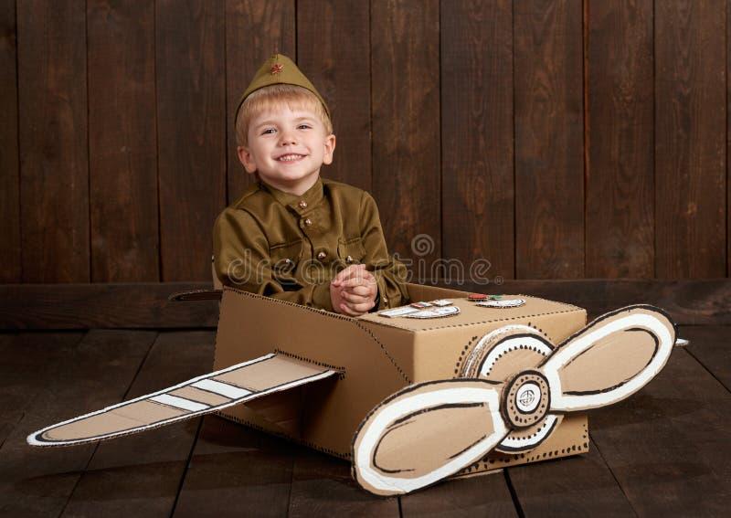 Visten al muchacho de los niños mientras que el soldado en uniformes militares retros se sienta en un aeroplano hecho de la caja  imagen de archivo