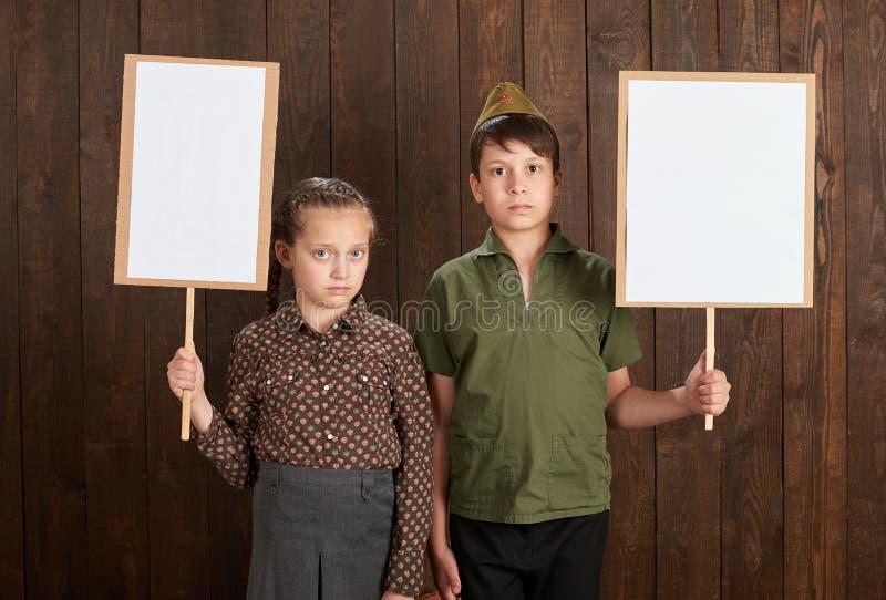 Visten a los niños en uniformes militares retros Ellos ` con referencia a sostener los carteles en blanco para los retratos de lo fotos de archivo