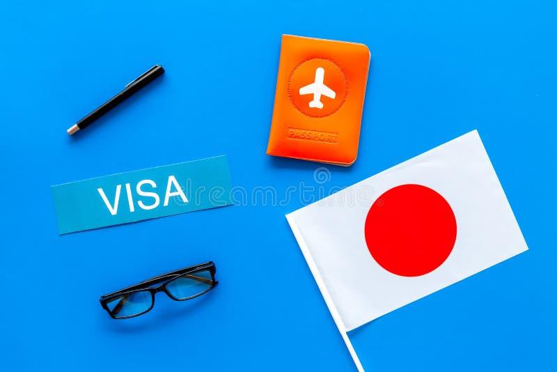 Visto ao conceito de Japão Visto do texto perto da tampa do passaporte e da bandeira japonesa na opinião superior do fundo azul fotografia de stock