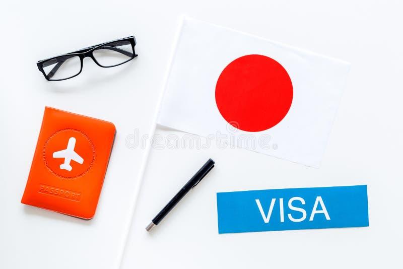 Visto ao conceito de Japão Visto do texto perto da tampa do passaporte e da bandeira japonesa na opinião superior do fundo branco foto de stock royalty free