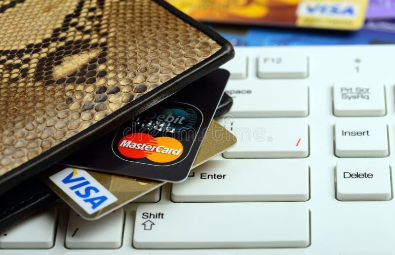 Visto e carte di credito di Mastercard in portafoglio sopra il taccuino keyboar fotografia stock