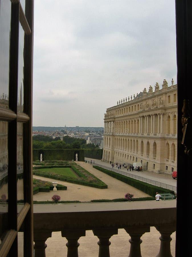 Visto por una ventana abierta del castillo de Versalles con su jardín francia imagen de archivo