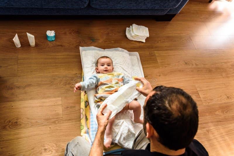 Visto sopra la faccia di un bambino sorridente mentre le mani di suo padre gli cambiano il pannolino sporco fotografia stock libera da diritti
