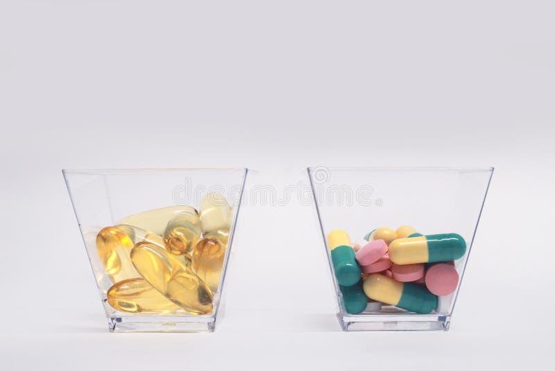 Vistraancapsules en tabletten in glaskoppen royalty-vrije stock afbeelding
