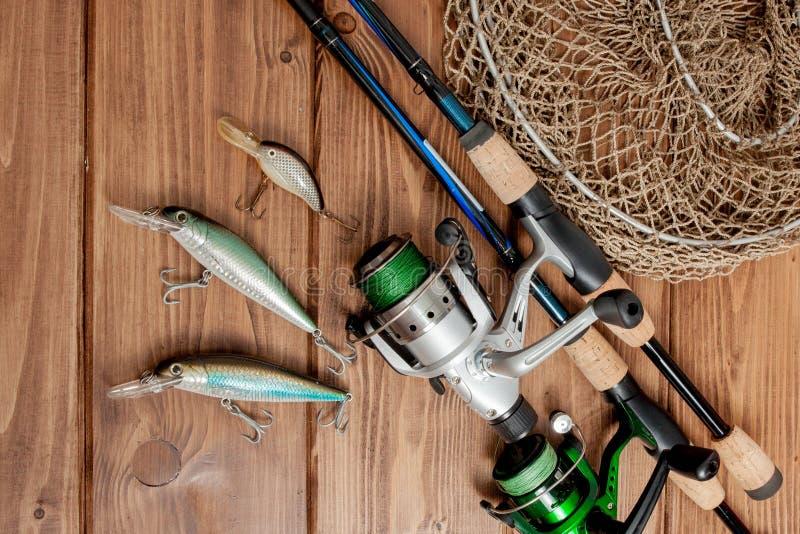 Vistuig - visserij het spinnen, haken en lokmiddelen op houten achtergrond met exemplaarruimte royalty-vrije stock foto's