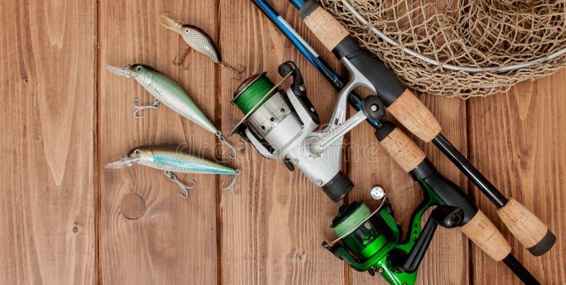 Vistuig - visserij het spinnen, haken en lokmiddelen op houten achtergrond met exemplaarruimte stock fotografie