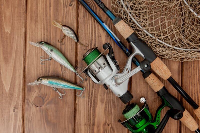 Vistuig - visserij het spinnen, haken en lokmiddelen op houten achtergrond met exemplaarruimte royalty-vrije stock afbeeldingen