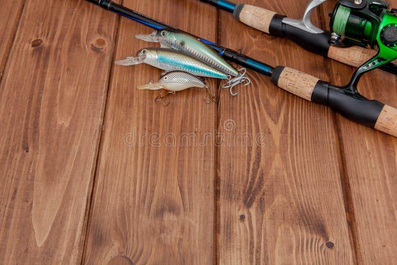 Vistuig - visserij het spinnen, haken en lokmiddelen op houten achtergrond met exemplaarruimte stock afbeeldingen