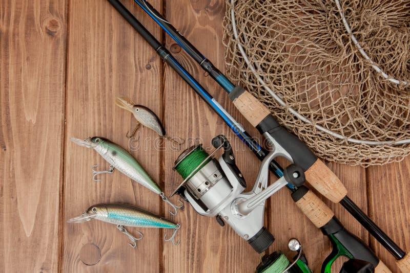 Vistuig - visserij het spinnen, haken en lokmiddelen op houten achtergrond met exemplaarruimte stock foto