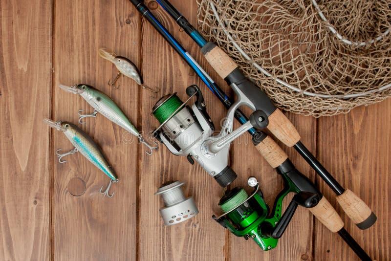 Vistuig - visserij het spinnen, haken en lokmiddelen op houten achtergrond met exemplaarruimte royalty-vrije stock afbeelding