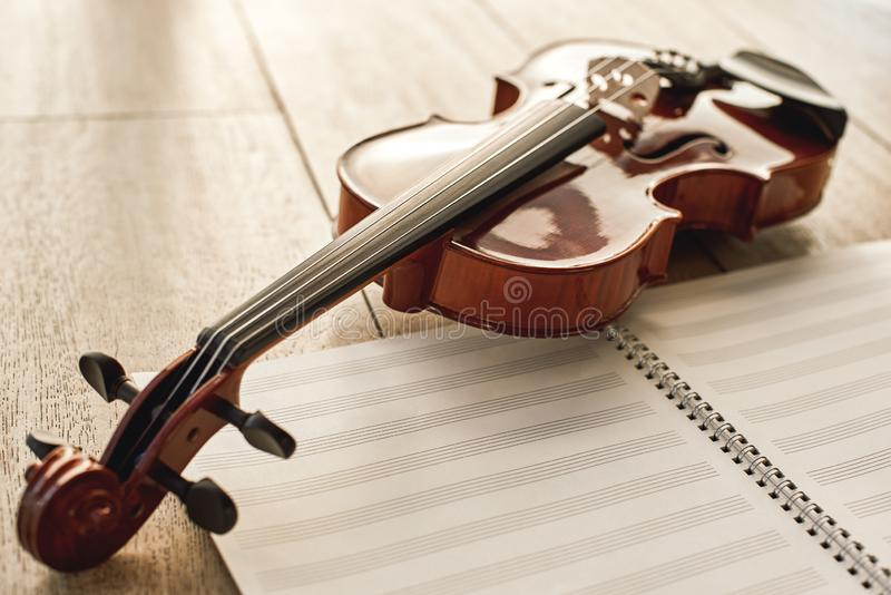 Visual beauty of classical instrument. Close up view of brown beautiful violin lying on sheets for music notes over stock photos