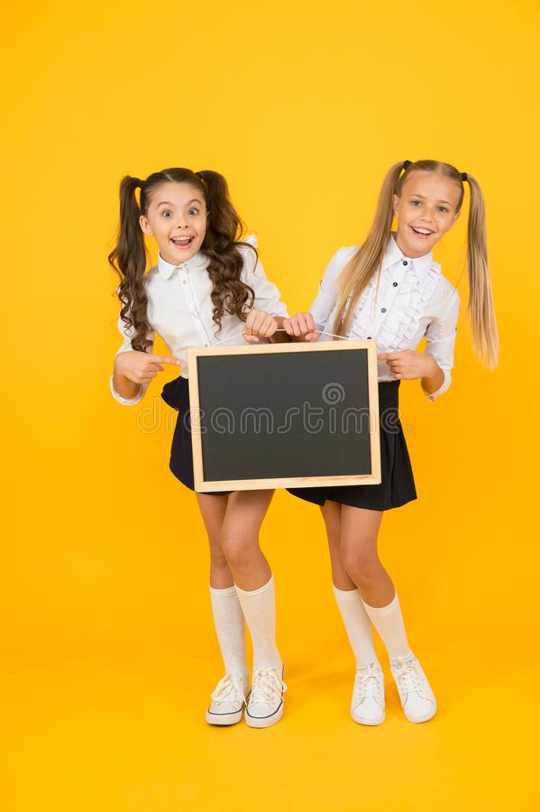 Visual communication. Girls school uniform hold blackboard. Back to school concept. Upcoming events in school. Glad to stock photos