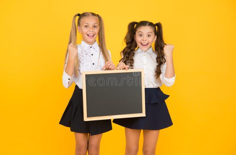 Visual communication. Glad to inform. Schoolgirls informing you. School girls hold blank chalkboard copy space. Girls. School uniform hold blackboard. Back to stock photography