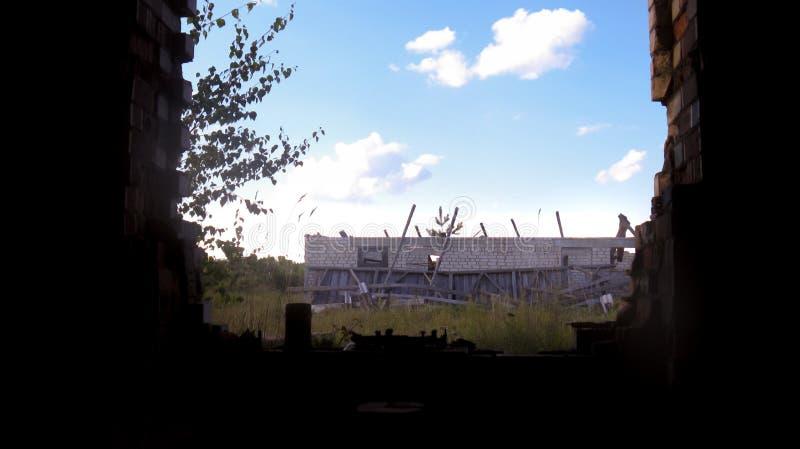 Visualizzazione dell'edificio in scatola non finito dalla finestra rovinata immagine stock libera da diritti
