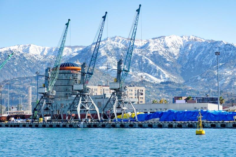 Visualizzazione di porto marittimo contro lo sfondo delle montagne innevate e del carico, gru di carico fotografia stock