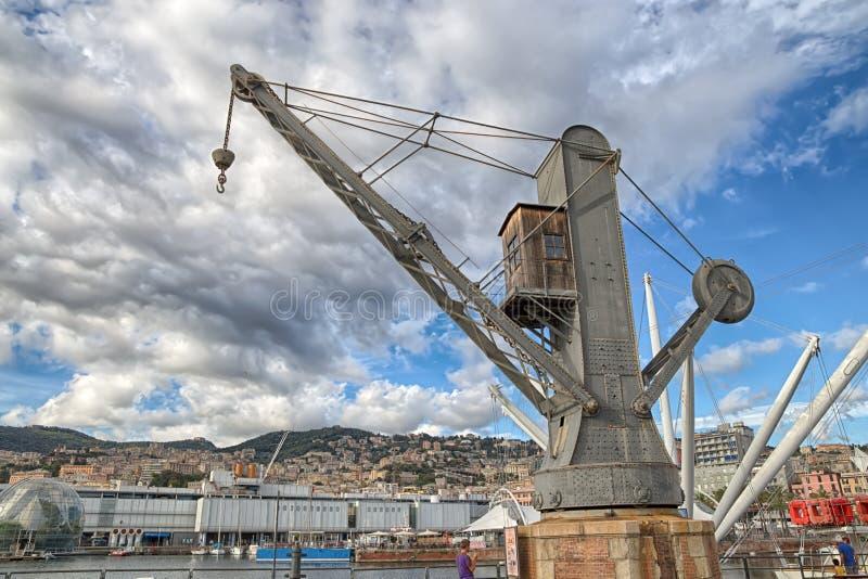 Visualizzazione di vecchia gru industriale nel porto antico di Genova, Italia, sotto un cielo nuvoloso fotografie stock