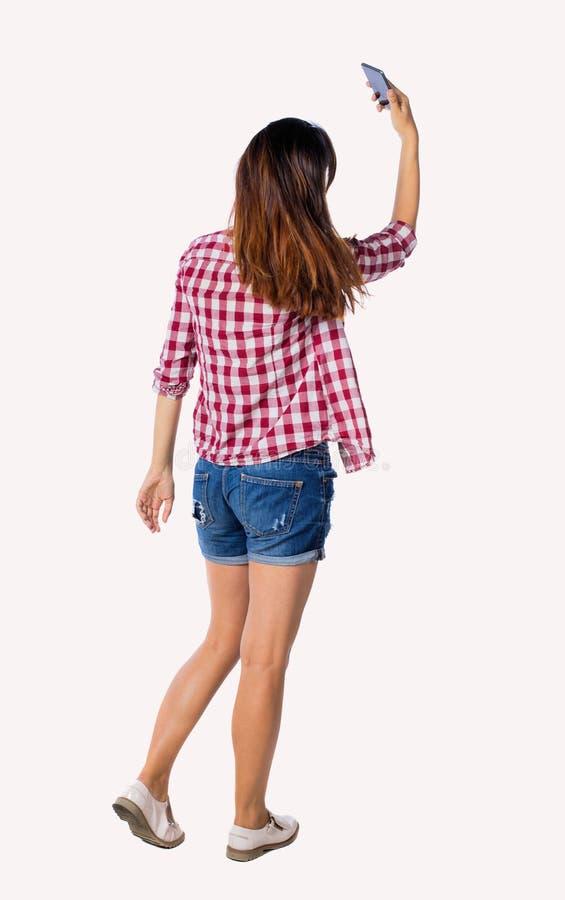 Visualizzazione posteriore di stare giovane bella ragazza con il computer della compressa nelle mani fotografia stock