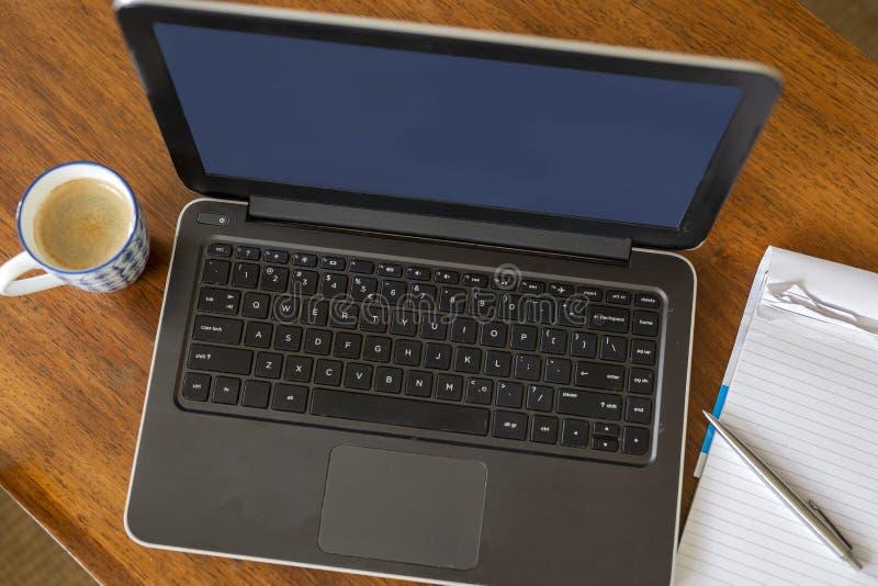 Visualizzazione superiore con la tavola della scrivania dello spazio della copia con il computer, rifornimenti, tazza di caffè fotografia stock