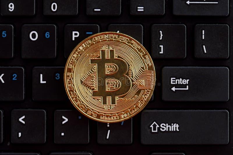 Visualizzazione superiore del bitcoin dorato della replica sulla tastiera di computer immagine stock