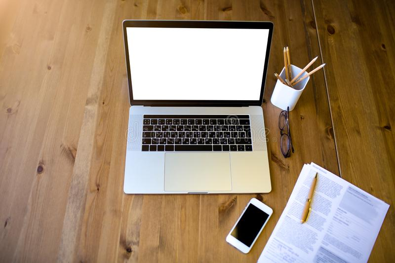 Visualizzazione superiore del posto di lavoro moderno con i documenti cartacei, i vetri, il telefono cellulare, le matite ed il c fotografia stock
