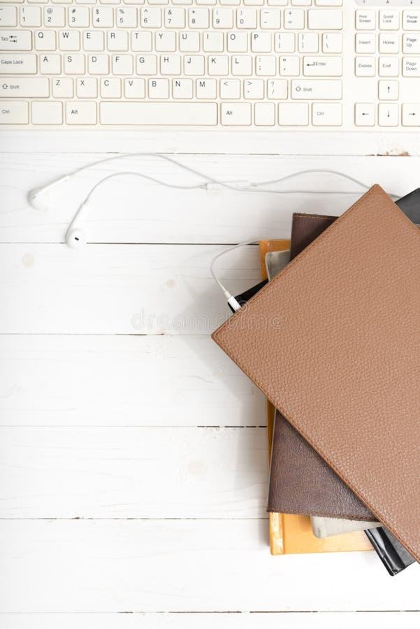 Visualizzazione superiore del trasduttore auricolare con la tastiera di computer con la pila di libro immagini stock libere da diritti