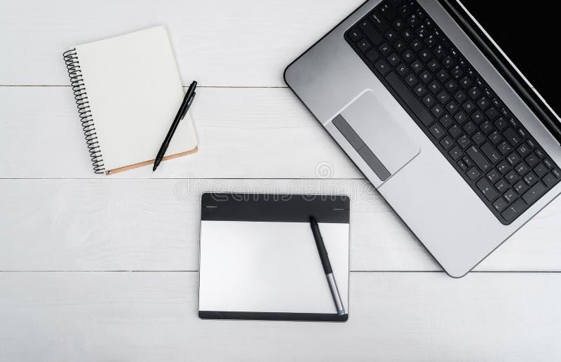 Visualizzazione superiore sulla tavola di legno bianca con il computer portatile in bianco aperto immagini stock