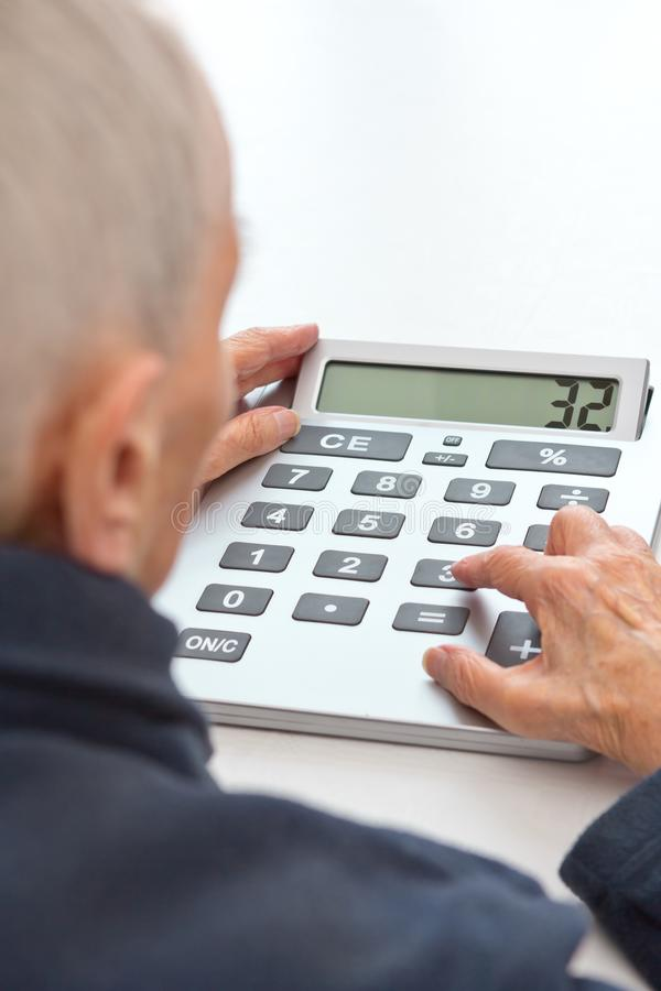 Visually handicapped person calcutator giant digits. Very old and visually impaired woman sitting at a table using a desktop calculator with an extra large stock images