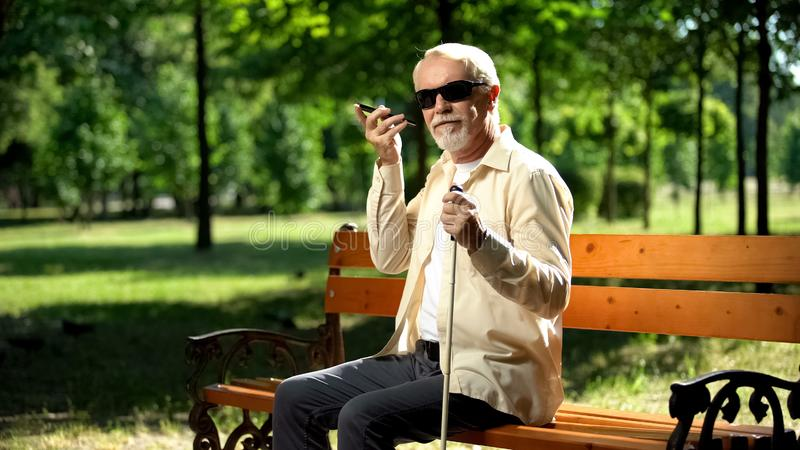 Visually impaired old man using voice control app in smartphone, innovations. Stock photo stock photo