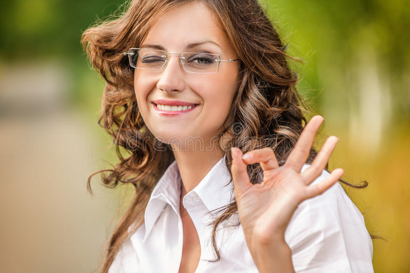 Vitória encantador do sinal das mostras dos vidros da jovem mulher do retrato imagem de stock royalty free