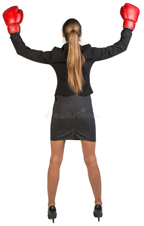 Vitórias vestindo das luvas de encaixotamento da mulher de negócios rear fotografia de stock