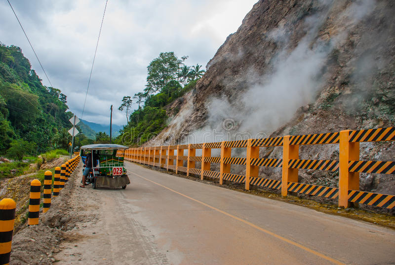 Vit ånga från berget av vulkan och korsar vägen med en motorcykel med en sidecar philippines Valencia ö Ne arkivbilder