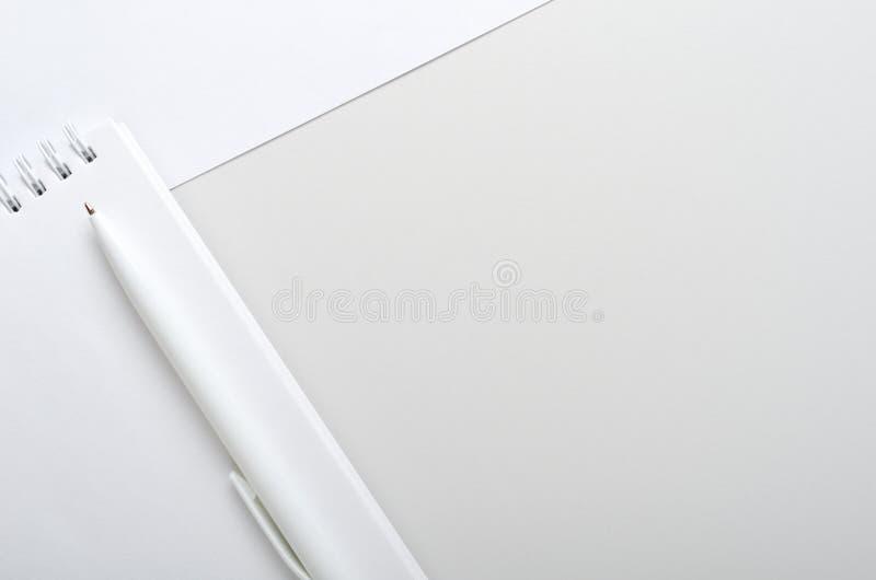 Vit öppen anteckningsbok med pennan på grå och vit bakgrund Begreppskontorsskrivbord, affär B?sta sikt, lekmanna- l?genhet, kopie royaltyfria foton