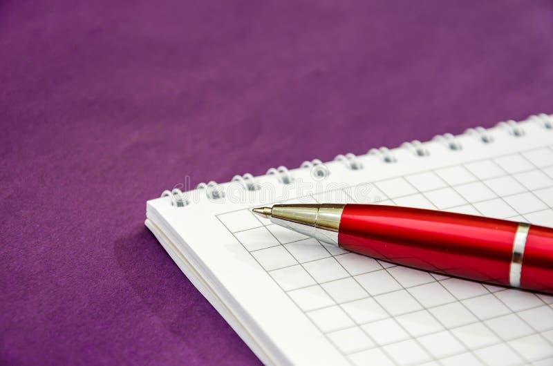 Vit anteckningsbok och pennnärbild arkivfoton