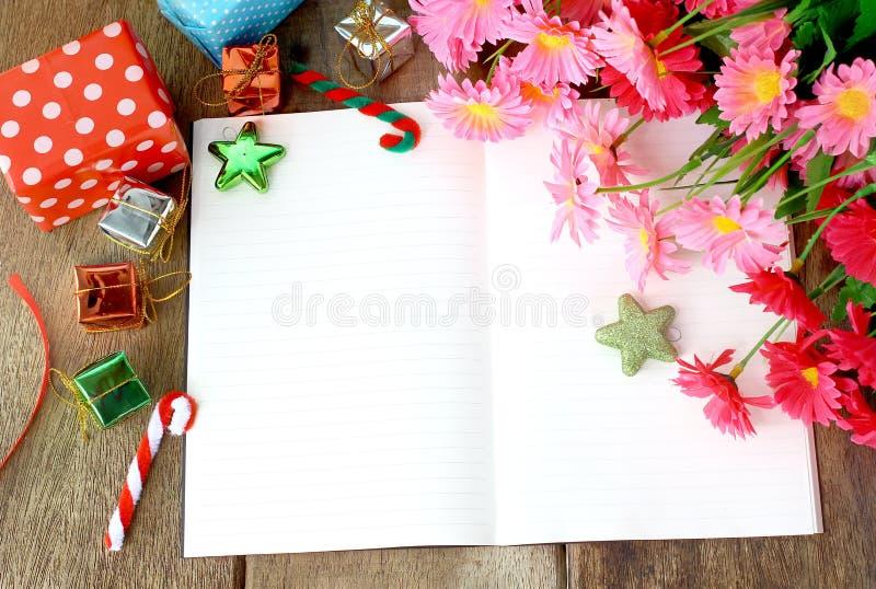 Vit anteckningsbokhälsning, härlig blomma och gåvaask för beröm på träbakgrund fotografering för bildbyråer