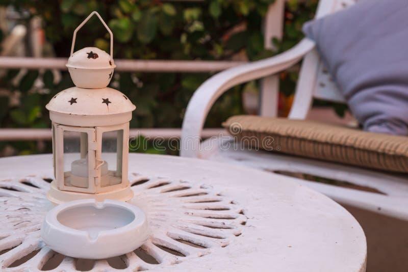 Vit bärbar lampa på metalltabellen i trädgården Garnering belysningsutrustning, inredesign, landskapsarkitektur fotografering för bildbyråer
