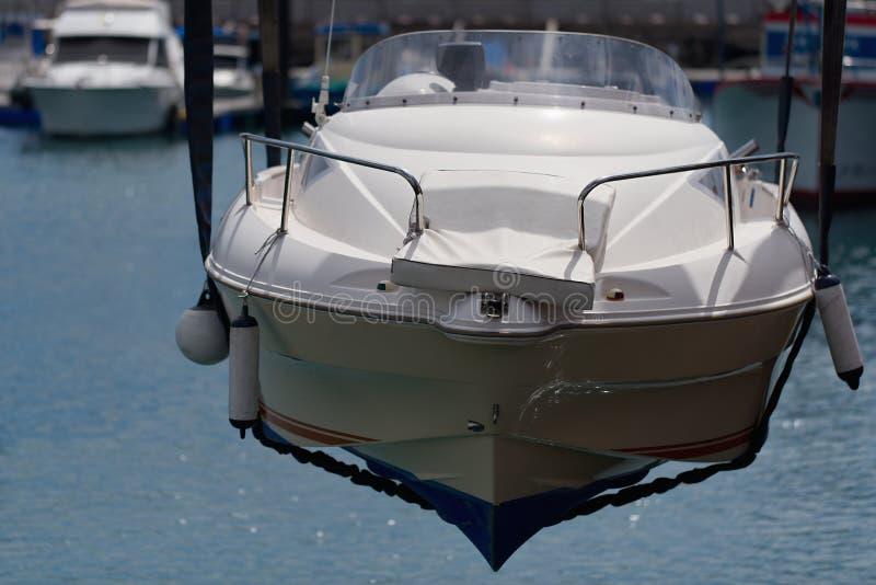 Vit båt stiger upp ur havet genom att använda kran fotografering för bildbyråer