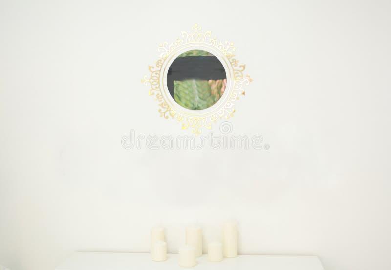 Vit backgroung med en spegel och stearinljus royaltyfri fotografi