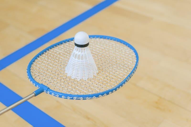 Vit badmintonfjäderboll på ett hallgolv på badmintondomstolar Stäng sig upp fjäderbollar på racketbadminton på badmintondomstolar royaltyfri bild