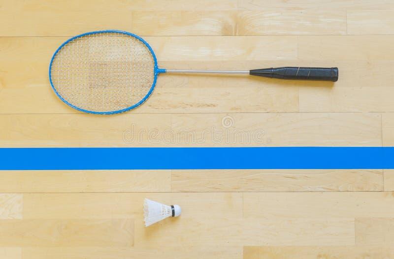 Vit badmintonfjäderboll på ett hallgolv på badmintondomstolar Stäng sig upp fjäderbollar på racketbadminton på badmintondomstolar arkivbild