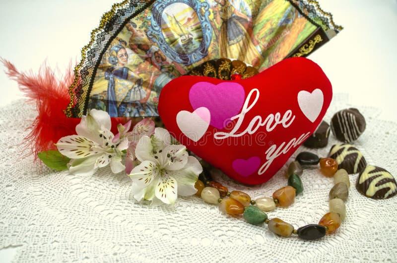 Vit bakgrund med den delikata vita servetten och röd hjärta med förälskelse snör åt du, bredvid pärlorna, fanen, godisen, blommor royaltyfri fotografi