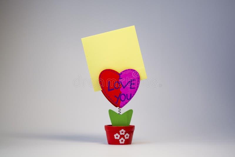 Vit bakgrund Trähjärta med en klädnypa för klistermärkear på en vår lyckönskan St Dag för valentin` s paper yellow royaltyfri fotografi