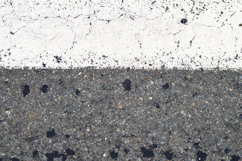 Vit bandvägteckning på asfaltvägen arkivbild