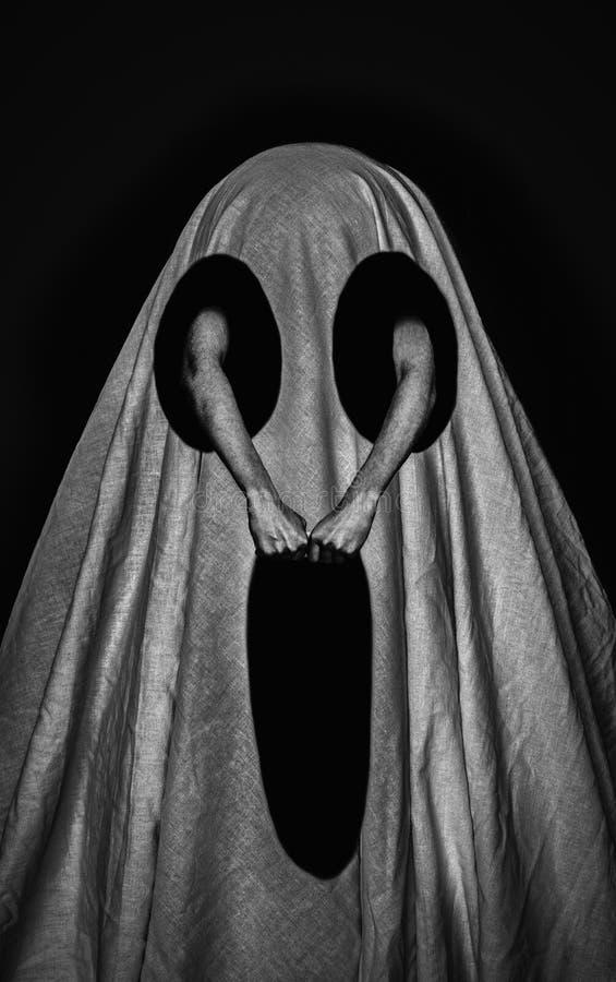 Vit bedsheet med tre svarta hål på mörk bakgrund som ett begrepp av en kuslig spöke arkivfoton