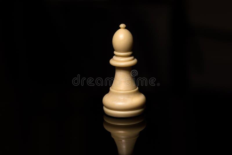 Vit biskop för klassiskt schack på det svarta brädet som isoleras arkivfoton