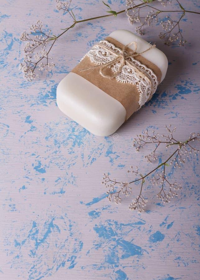 Vit blom- handgjord tvål från naturliga råvaror på ett ljust - blått fotografering för bildbyråer