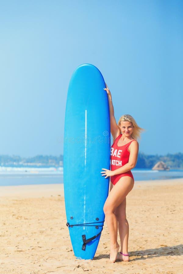 Vit blond surfareflicka i röd surfingbräda för baddräktinnehavblått royaltyfri bild
