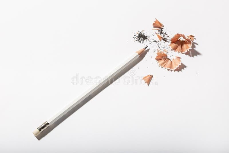 Vit blyertspenna med att vässa shavings på vit bakgrund Tillbaka till skola eller det arbetande begreppet arkivbild