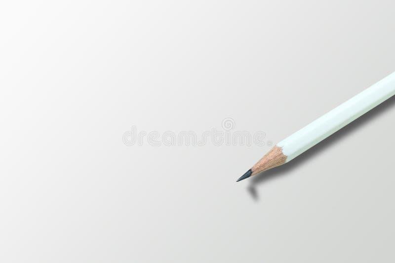 Vit blyertspenna på grått golv med skugga av det brutna huvudet av den skarpa blyertspennan arkivbild