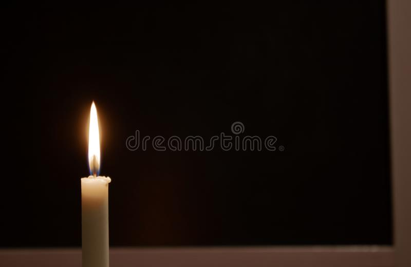 Vit bränningstearinljus på en svart bakgrund Sörja brinnande stearinljus fotografering för bildbyråer