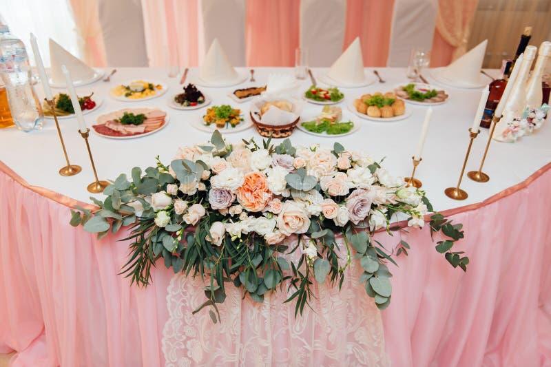 Vit bröllopbåge som dekoreras med den inomhus blomman arkivbilder